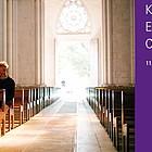 Ein Mann sitzt in einer Kirche, das Hauptportal ist weit geöffnet.