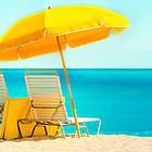 Zwei Liegestühle und Sonnenschirm am Strand