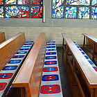 Kirchenbänke mit Sitzauflagen. Die Sitzauflagen zeigen Steckdosen.