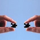 Zwei Hände halten jeweils ein Puzzleteil.