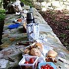 Auf einer Steinmauer stehen Getränke und Essen.