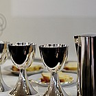 Abendmahlkelche und Schalen mit Brot auf dem Altar.