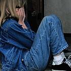 Ein trauriges Mädchen sind in einem alten Hauseingang und verbirgt sein Gescht mit den Händen.