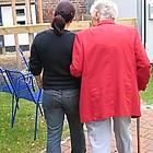 Seniorin auf Spaziergang mit Begleiterin.