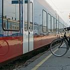 Radfahrerin steht auf dem Bahnsteig, stehender Nahverkehrszug