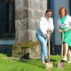 Zwei Frauen mit Spaten auf einer Wiese vor einer Kirche