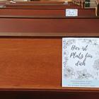 Kirchenbänke mit Hinweisschildern: Hier ist Platz für dich - Nebeneinander sitzen können Menschen, die in einem Haushalt leben.