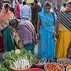Frauen in Saris betrachten Gemüse, das auf dem Boden ausgelegt wurde.