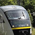 Zug der Hessischen Landesbahn fährt durch grüne Landschaft