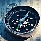 Ein Kompass liegt auf einer Zeitungsseite mit Aktioenkursen.