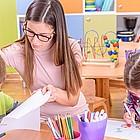Erzieherin und zwei Kinder beim Basteln im Kindergarten