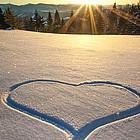 Schneefläche im Gebirge mit Spur in Herzform