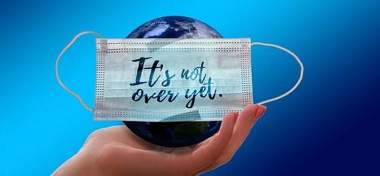 Bildmontage: Hand mit Erdball in der Hand, mit Coronamaske auf der steht: It's not over yet