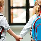 Kindergartenkinder, ein Junge und ein Mädchen, laufen Hand in Hand