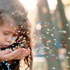 Mädchen pustet Konfetti