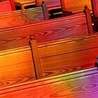 Leere Kirchenbänke in bunten Farben angestrahlt