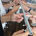 Mehrere Personen halten einen Aluminiumstab mit ihren Fingern und senken ihn dann gleichzeitig ab.