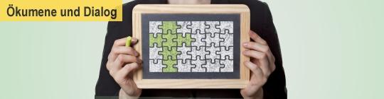 Frau Halt ein Puzzle hoch, einige Teile sind grün markiert und bilden ein Kreuz